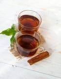 Szklana filiżanka herbata z cynamonowymi kijami Zdjęcie Royalty Free