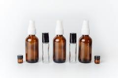 Szklana kiść i Rolkowy próbek butelek Fonu bielu tło obraz stock