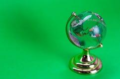 Szklana kula ziemska z ocenionymi kontynentami na zielonym tle zdjęcie stock