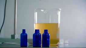 Szklana miara filiżanki z pomarańczowym cieczem i trzy butelki zbliża je zdjęcie wideo