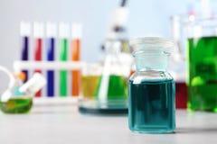 Szklana odczynnik butelka i inny glassware na stole w chemii laboratorium obraz royalty free