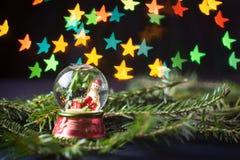Szklana piłka z bałwanem i gwiazdą kształtował bokeh Obrazy Stock