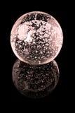 Szklana piłka z wewnętrznymi bąblami na czarnej lustro powierzchni Zdjęcie Stock