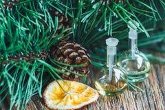 Szklane butelki istotny olej z sosnowymi rożkami, pomarańczami i jodeł gałąź na drewnianym tle, Zdjęcia Stock