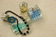 Szklane butelki z barwionym pachnidłem i czarni koraliki na szarym tle zdjęcie royalty free