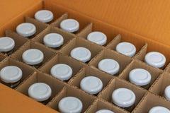 Szklane butelki z białymi butelek nakrętkami w kartonie, wierzchołek rywalizują obrazy stock