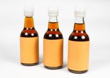 Szklane butelki z cieczem, Pustą etykietką i Plastikową nakrętką, Fotografia Stock