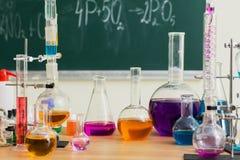 Szklane kolby z barwiącymi cieczami przy chemii lekcją obraz stock
