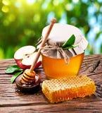 Szklane puszki pełno miód, jabłka i honeycombs, zdjęcie royalty free