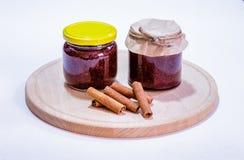 Szklani słoje truskawkowy dżem i cynamonowi kije na drewnianym talerzu Obrazy Stock