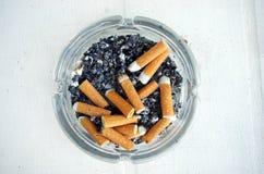 Szklany ashtray z papierosowymi kruponami zdjęcie royalty free