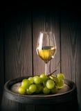 Szklany biały wino z wiązką dojrzali winogrona Obraz Stock