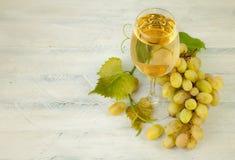 Szklany biały wino z winogronami i liściem na drewnianej desce Zdjęcia Stock