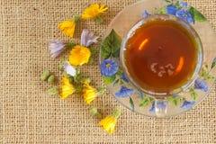 Szklany kubek herbata z żółtym i błękitem kwitnie Fotografia Stock