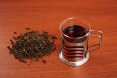 Szklany kubek i polana herbata na stole Zdjęcie Stock