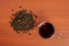 Szklany kubek i polana herbata na stole Zdjęcia Stock