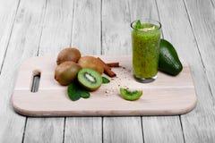 Szklany pełny zielony smoothie od kiwi owoc z ziarnami, avocado, orzechami włoskimi, cynamonem i mennicą na świetle drewnianym cz Obrazy Royalty Free