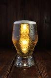 Szklany piwo na ciemnym drewno stole Pionowo orientacja Zdjęcie Stock