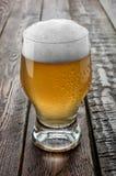 Szklany piwo na drewno stole Zdjęcia Royalty Free