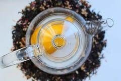 Szklany przejrzysty teapot na bia?ym stole i rozpraszaj?cy woko?o czarnej herbaty z additives zdjęcia royalty free