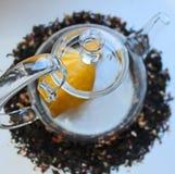 Szklany przejrzysty teapot na bia?ym stole i rozpraszaj?cy woko?o czarnej herbaty z additives zdjęcia stock