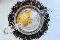 Szklany przejrzysty teapot na bia?ym stole i rozpraszaj?cy woko?o czarnej herbaty z additives fotografia stock
