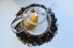 Szklany przejrzysty teapot na bia?ym stole i rozpraszaj?cy woko?o czarnej herbaty z additives obraz stock