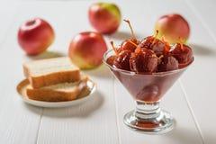 Szklany puchar cały Jabłczany dżem i świezi jabłka na drewnianym stole obraz royalty free