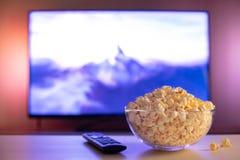Szklany puchar popkorn i pilot do tv w tle TV pracuje Evening wygodnego dopatrywanie w domu film lub seriale telewizyjni fotografia stock
