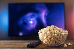 Szklany puchar popkorn i pilot do tv w tle TV pracuje Wieczór wygodny dopatrywanie film lub seriale telewizyjni przy obrazy stock