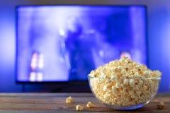 Szklany puchar popkorn i pilot do tv w tle TV pracuje Wieczór wygodny dopatrywanie film lub seriale telewizyjni przy zdjęcie royalty free