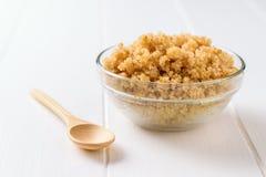 Szklany puchar z gotowanym quinoa i drewnianą łyżką na bielu stole Bezpłatny gotowany zboża naczynie zdjęcie royalty free