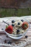 Szklany puchar z śniadaniem: oatmeal, truskawki i czarne jagody, Fotografia Stock