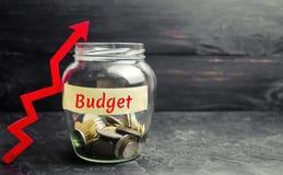 Szklany słój w górę strzały i z monetami i «budżetem «wpisowym Pojęcie biznesowy sukces, pieniężny przyrost i bogactwo, Increa zdjęcie stock