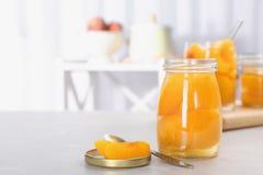 Szklany słój z chronić brzoskwini połówkami na stole zdjęcia stock