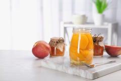 Szklany słój z chronić brzoskwini połówkami na stole zdjęcie stock