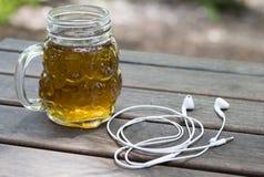 Szklany słój z herbatą i hełmofonami na drewnianym tle zdjęcia royalty free
