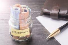 Szklany słój z monetami i euro banknoty z słowami edukacje Pióro, pusty prześcieradło papier i skóra portfel, zdjęcia stock