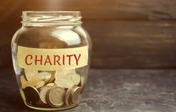 Szklany słój z monetami i słowo dobroczynnością Pojęcie skumulowanie pieniądze dla darowizn oszczędzanie Ogólnospołeczna medyczna obraz stock