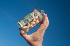 Szklany słój z pieniądze w ręce Fotografia Stock