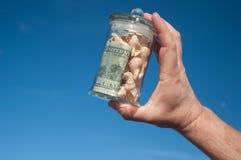 Szklany słój z pieniądze w ręce Obrazy Stock