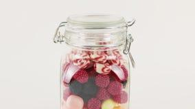 Szklany słój z wiele jaskrawymi słodkimi cukierkami zbiory