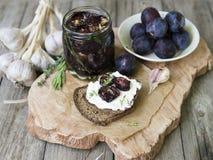 Szklany słój z wysuszonymi śliwkami i świeżymi rozmarynami na drewnianej porci desce, selekcyjna ostrość zdjęcie stock