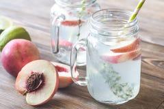 Szklany słój wapno woda z plasterkami brzoskwinia Zdjęcie Stock