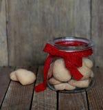 Szklany słój z ciastkami na tle drewno Zdjęcia Royalty Free