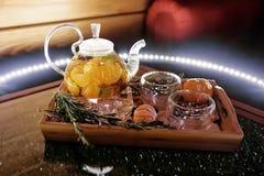 Szklany teapot z gorącą herbatą z tangerines na drewnianej tacy Fotografia Stock