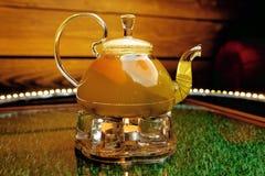 Szklany teapot z gorącą pomarańczową herbatą z pomarańczowymi plasterkami Obrazy Stock
