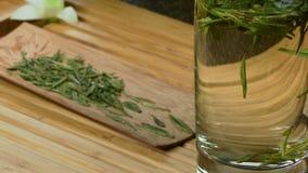 Szklany teapot z kwitnącym herbacianym kwiatem inside przeciw drewnianego tła zielonej herbaty Chińskim liściom zamyka up w trady Zdjęcie Stock