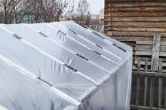 Szklarnia dla narastających warzyw w ogródzie Zakrywający z polietylenu filmem konserwować wilgoć i upał na tle fotografia royalty free