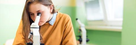Szkoła Średnia żeński uczeń w zajęcia z biologii Studencki używa mikroskop egzamininować próbki fotografia royalty free